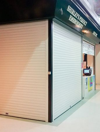 Foam filled roller shutters at right angles securing a corner store