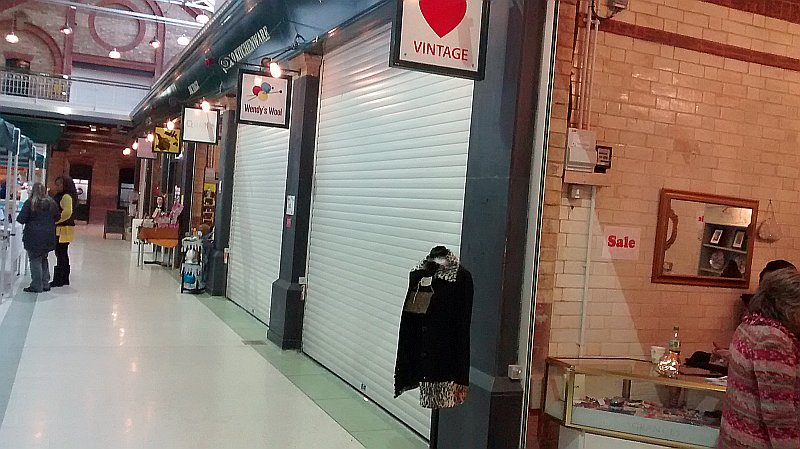 Pair of closed shutters with a third one opened in a shopping centre