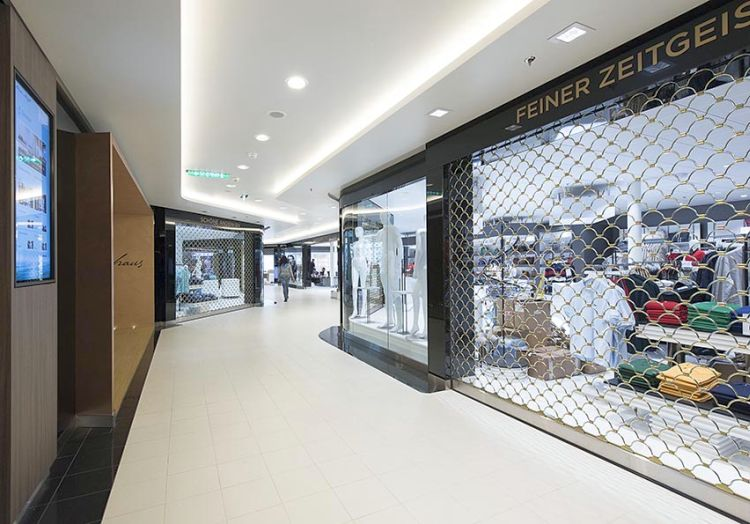 Gold plated armourshield roller grilles installed at different shops in a shopping centre.