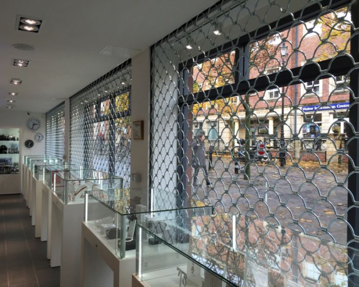 Looking out from a jewellery shop, through a closed roller grille