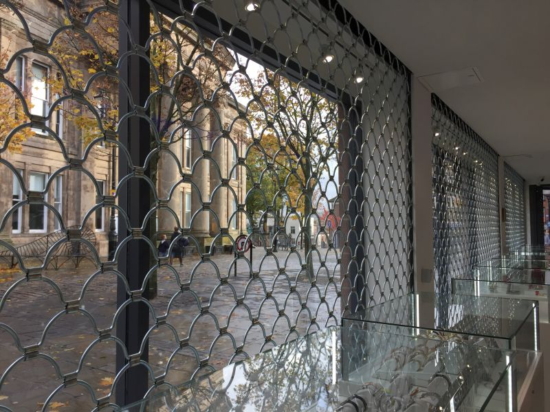8MM Silver style armourshield roller grille installed behind glass windows at a jewellery store.