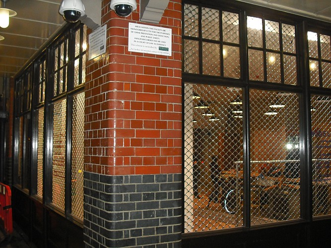 Armourshield roller grilles installed behind the windows of an office.