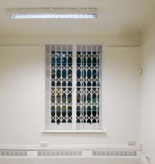 Retractable grille on the inside of a window