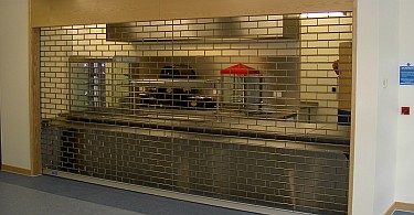 Roller grille in front of food servery.
