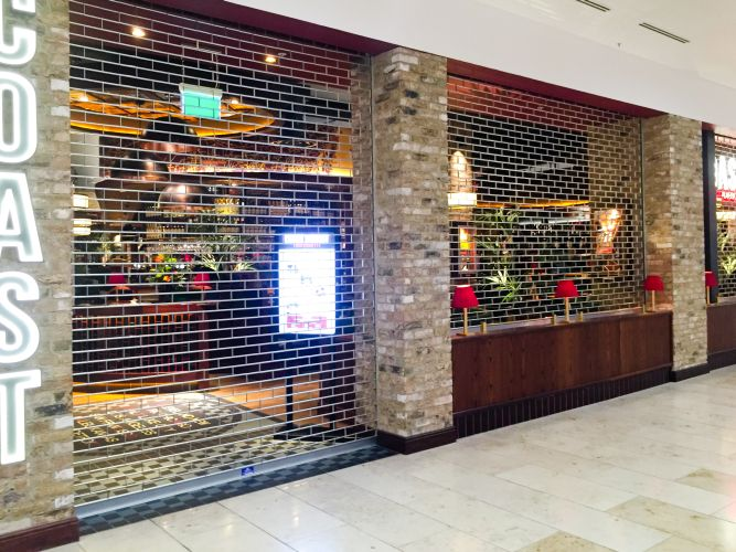 chainlink roller grilles across restaurant entrance and seating area