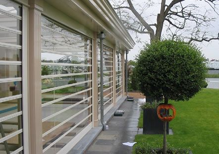 Polycarbonate shutters covering a patio area.
