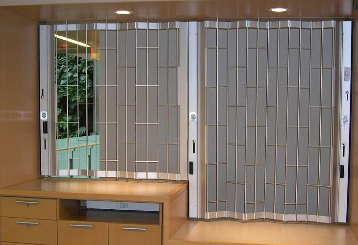 Sliding shutter at a reception desk with a section for disabled people.