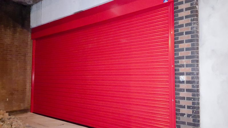 Red heavy duty electronic security roller shutter in a brick wall