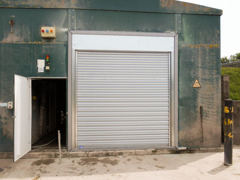 Industrial roller shutter on a utility building with a pedestrian access door next to it.