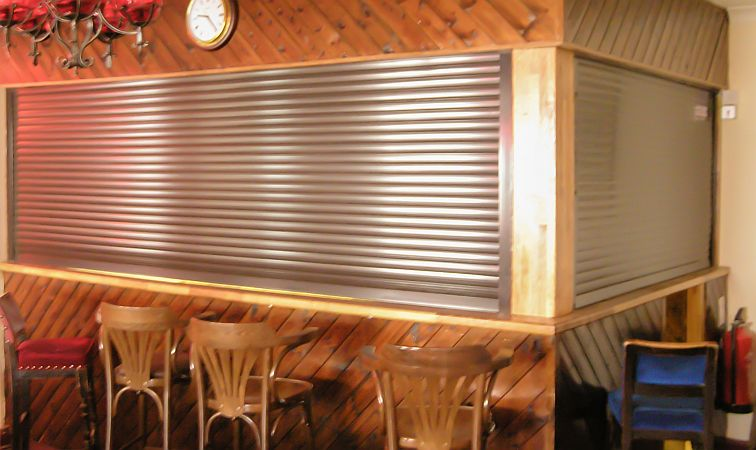 A pair of aluminium roller shutters on a bar at right angles