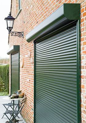 green aluminium roller shutters installed over a door and window of a house