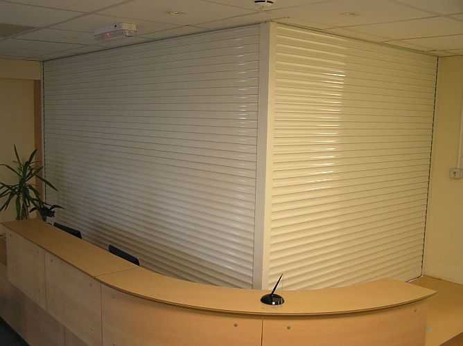 Angled pair of aluminium roller shutters at a reception desk.