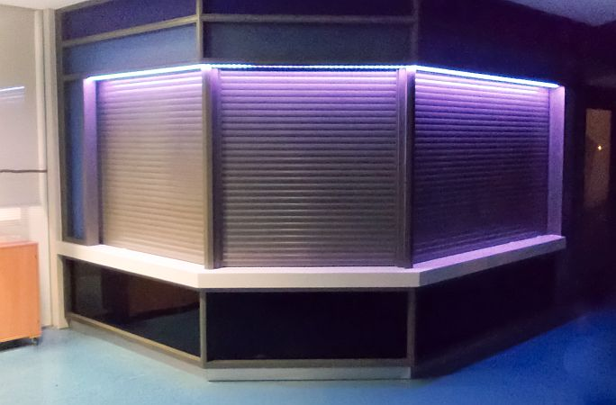 Three aluminium security shutters at 45 degree angles on a reception desk