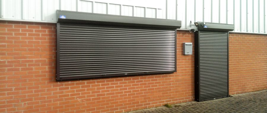 Closed aluminium security shutters on a window and door to a warehouse