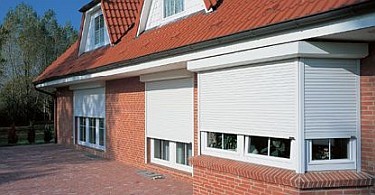 White aluminium roller shutters in front of the windows of a house.
