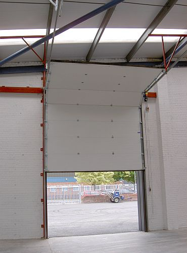 An overhead sectional door in a warehouse halfway opened.