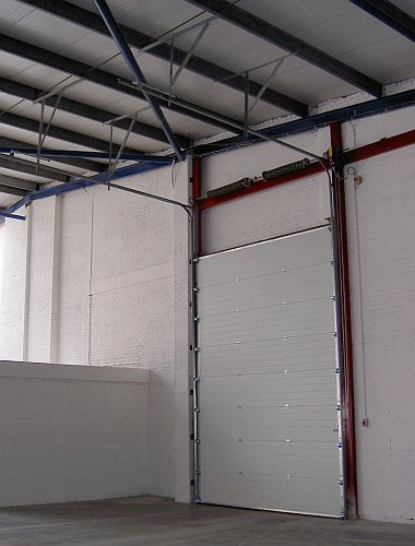 A closed overhead sectional door seen from inside a warehouse.