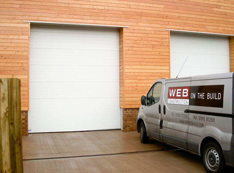 A white sectional door on the outside of a warehouse