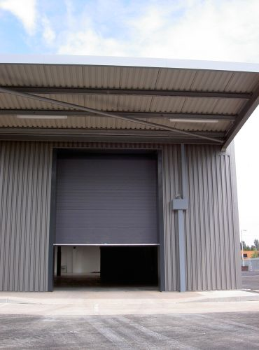 Large up and over sectional insulated shutter door over the entrance of a warehouse storage area.
