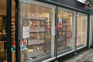 Security roller grilles placed behind the glass of a shop front.