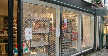 Three security roller grilles in a shopfront window display behind glass.