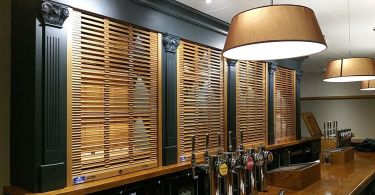 A row of real wood roller shutters with an open curtain installed behind a bar.