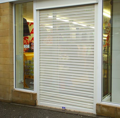 Perforated roller shutter with sloping buttom rail reveal fitted to shopfront entrance.