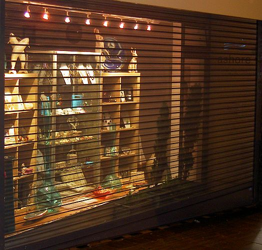 Transparent effect of viewguard roller shutter lit from behind in a window display at night.
