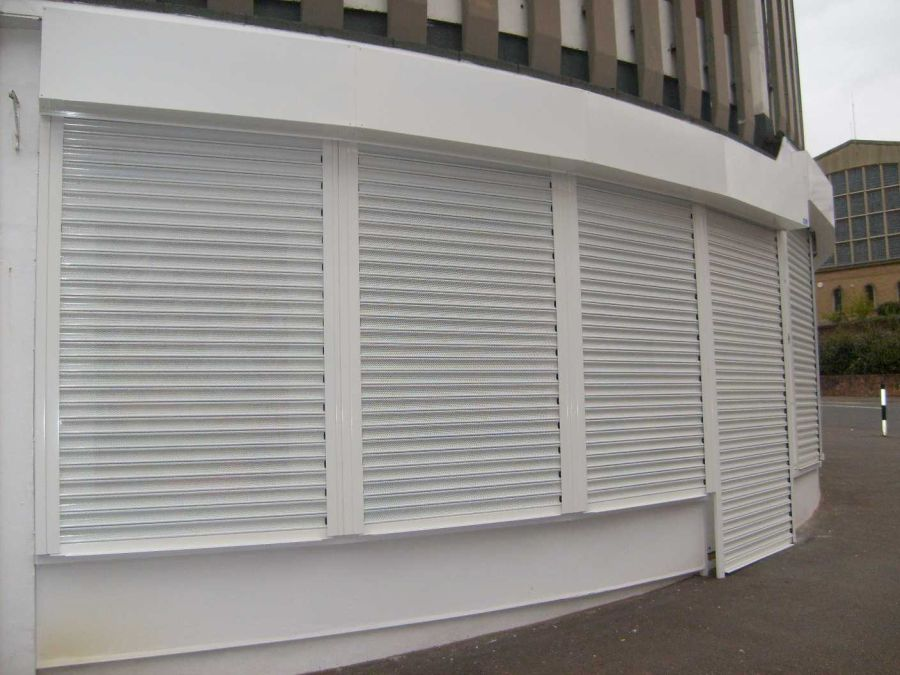 Angled roller shutters over  acurved opening.