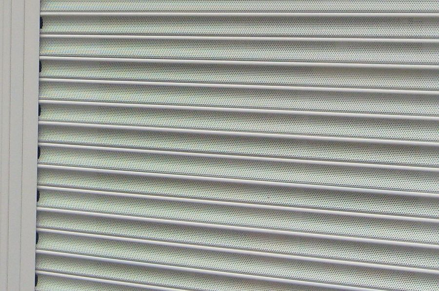 Profile detail of white, perforated steel roller shutter lath