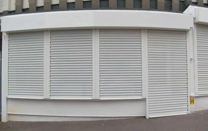 Perforated steel roller shutters painted white