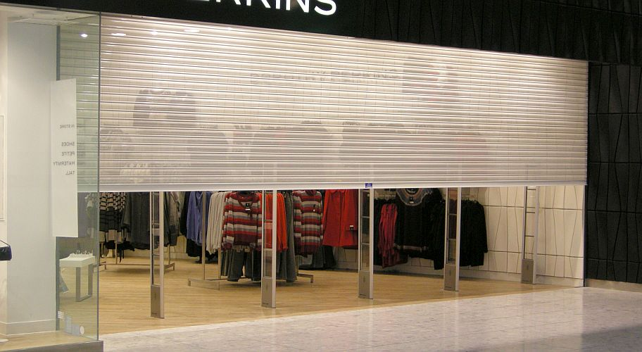 Closing roller shutter in shopping centre.
