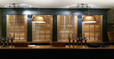 A wooden roller shutter with an open style curtain installed on a bar.